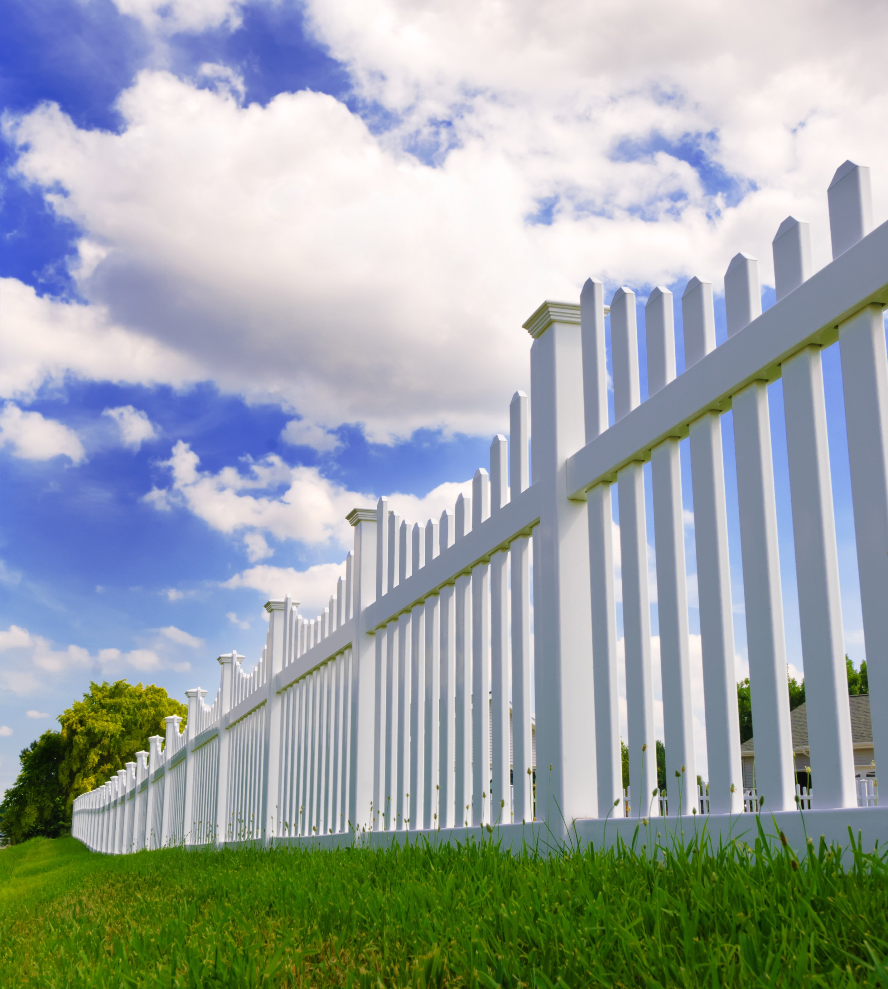 Contemporary white vinyl fence spanning across a homes backyard with grass and blue sky and clouds in the background